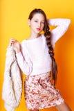 Belle fille mignonne de mode adolescente dans un chandail et un skir sur le fond jaune avec la longue pose de cheveux Images libres de droits
