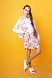 Belle fille mignonne de mode adolescente dans un chandail et un skir sur le fond jaune avec la longue pose de cheveux Photo libre de droits
