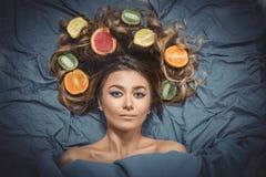 Belle fille modèle magnifique avec les fruits sains d'agrume coloré dans ses cheveux brillants Soin et produits capillaires Conce Photographie stock libre de droits