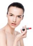 Belle fille modèle tenant le maquillage de tube de rouge à lèvres Images stock