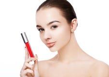 Belle fille modèle tenant le rouge à lèvres rouge liquide photographie stock