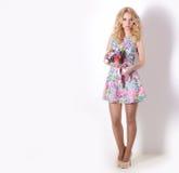Belle fille modeste d'offre de bonbon avec les cheveux blonds bouclés se tenant sur le fond blanc avec un bouquet des fleurs Images libres de droits
