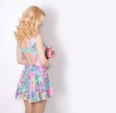 Belle fille modeste d'offre de bonbon avec les cheveux blonds bouclés se tenant sur le fond blanc avec un bouquet des fleurs Image stock