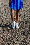 Belle fille noire adolescente dans la jupe bleue et des espadrilles blanches dessus Images libres de droits