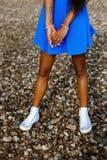Belle fille noire adolescente dans la jupe bleue et des espadrilles blanches dessus Photographie stock