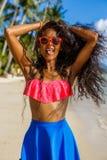 Belle fille noire adolescente dans la jupe bleue et soutien-gorge rose sur le b Images libres de droits
