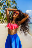 Belle fille noire adolescente dans la jupe bleue et soutien-gorge rose sur le b Photos stock