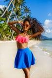 Belle fille noire adolescente dans la jupe bleue et soutien-gorge rose sur le b Image stock