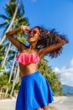 Belle fille noire adolescente dans la jupe bleue et soutien-gorge rose sur le b Photographie stock libre de droits