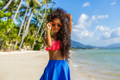 Belle fille noire adolescente dans la jupe bleue et soutien-gorge rose sur le b Image libre de droits