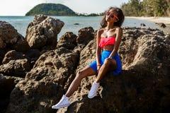 Belle fille noire adolescente dans la jupe bleue et soutien-gorge rose sur le r Image libre de droits