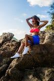 Belle fille noire adolescente dans la jupe bleue et soutien-gorge rose sur le r Images stock