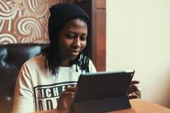 Belle fille noire souriant et travaillant au comprimé en café Images stock