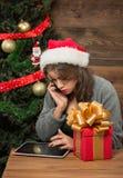 Belle fille parlant au-dessus du mobile et à l'aide du PC de table près de l'arbre de nouvelle année Photos libres de droits