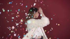 Belle fille parmi des confettis de couleur, mouvement lent Danse sexy de femme parmi des confettis au-dessus de fond rouge banque de vidéos
