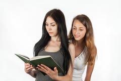 Belle fille piaulant dans le livre de l'amie Image libre de droits