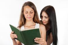 Belle fille piaulant dans le livre de l'amie Photographie stock libre de droits