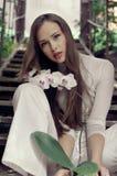 Belle fille posant avec la fleur d'orchidée Image libre de droits