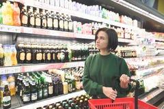 Belle fille posant dans un supermarché sur le fond des étagères avec des produits photographie stock