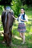 Belle fille près de cheval brun Image stock