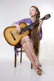 Belle fille qui joue la guitare Photo stock