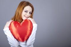 Belle fille red-haired avec le coeur de jouet. Images stock