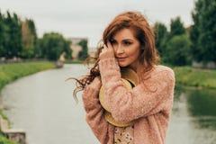 Belle fille red-haired photo dans la perspective de la rivière, l'eau, lac en parc, été tristesse, attente photos libres de droits