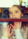 Belle fille regardant à l'extérieur l'hublot Image stock