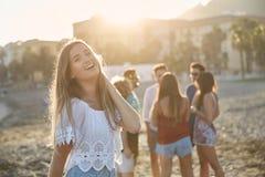 Belle fille riant sur la plage avec des amis derrière Images libres de droits
