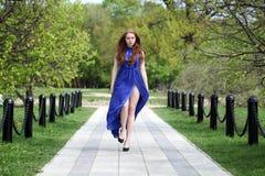 Belle fille rouge de cheveux dans une robe bleue photo libre de droits