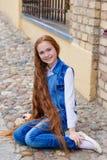 Belle fille rousse avec de longs cheveux jusqu'aux genoux Image stock