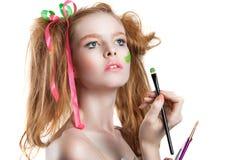 Belle fille rousse avec des rubans dans le volosah Coiffure et maquillage de Kreativnaya Une fille tenant une brosse et des peint Image libre de droits