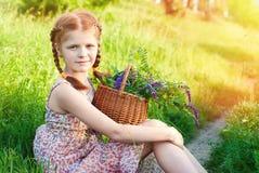 Belle fille rousse avec le panier de fleurs dans l'herbe verte Photographie stock