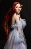 Belle fille rousse sexy avec de longs cheveux dans le coton de robe rétro Verticale de femme sur le fond noir Yeux profonds Beaut Photo stock