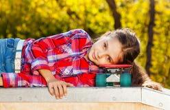 Belle fille s'étendant avec la tête sur la planche à roulettes Image libre de droits