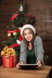Belle fille s'asseyant à la table avec une tablette près de l'arbre de nouvelle année Photographie stock libre de droits