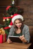Belle fille s'asseyant à la table avec une tablette près de l'arbre de nouvelle année Image libre de droits