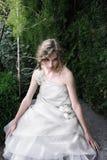 Belle fille s'asseyant dans le jardin Photos libres de droits