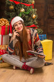 Belle fille s'asseyant près de l'arbre de nouvelle année avec une tablette Photographie stock libre de droits