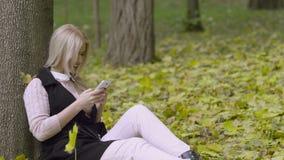Belle fille s'asseyant sous un arbre en parc d'automne avec un téléphone portable dans des ses mains banque de vidéos