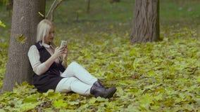 Belle fille s'asseyant sous un arbre en parc d'automne souriant et lisant des messages avec un téléphone portable dans des ses ma clips vidéos