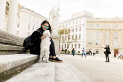 Belle fille s'asseyant sur des escaliers avec son chien après promenade dedans Photographie stock libre de droits
