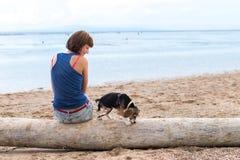 Belle fille s'asseyant sur la plage avec un chiot de chien de briquet Île tropicale Bali, Indonésie Images stock