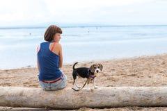 Belle fille s'asseyant sur la plage avec un chiot de chien de briquet Île tropicale Bali, Indonésie Photo libre de droits