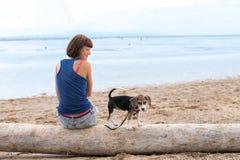 Belle fille s'asseyant sur la plage avec un chiot de chien de briquet Île tropicale Bali, Indonésie Photos libres de droits
