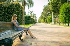 Belle fille s'asseyant sur le banc, la femme châtain dans la robe rayée, le style de vie à la mode avec votre téléphone Image stock