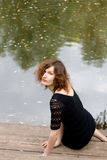 Belle fille s'asseyant sur le côté d'un étang Images libres de droits