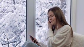 Belle fille s'asseyant sur le rebord de fenêtre, utilisant le smartphone avec des écouteurs L'hiver à l'extérieur clips vidéos