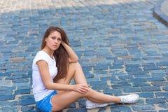 Belle fille s'asseyant sur le trottoir Image libre de droits