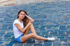 Belle fille s'asseyant sur le trottoir Image stock